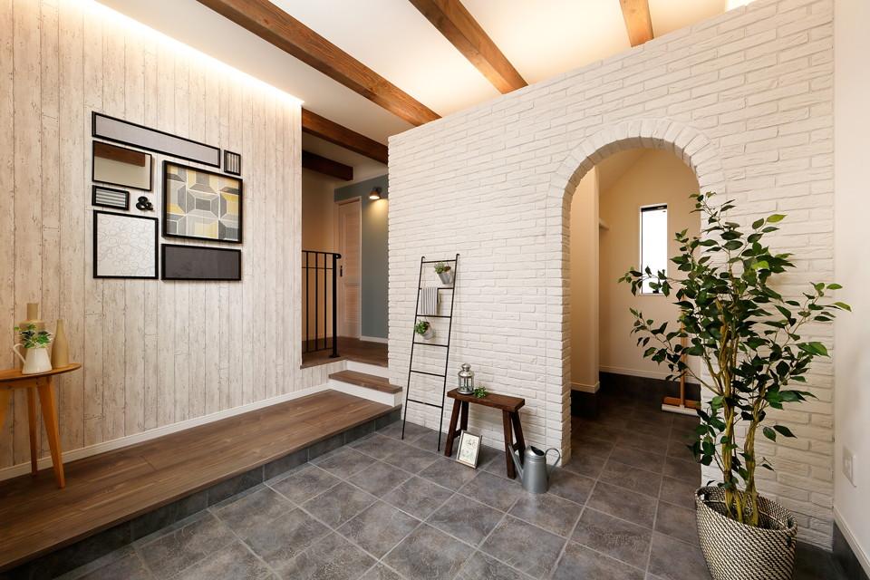 広々とした玄関スペースのアーチを抜けるとシューズクロークがあり収納力たっぷり!ホワイトの木目調クロスやアーチ部分のレンガはカラーを統一し素材を変化させることで全体的に統一感のある空間に。
