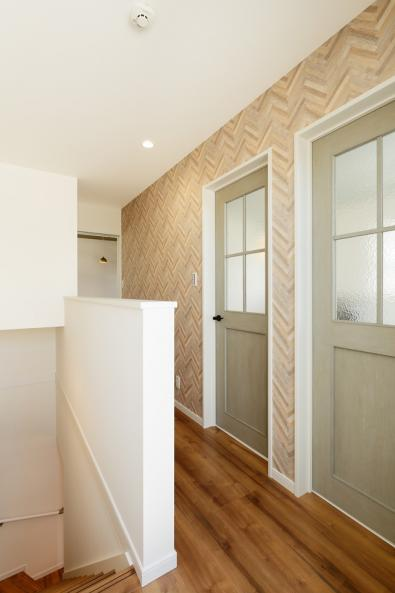 3階廊下の壁面は柔らかなウッド調のクロスがアクセントに。2つ並んだ子供部屋グリーンの扉は擦りガラスで光が抜けるので廊下の圧迫感も軽減。