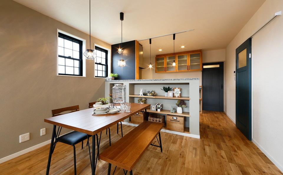 無垢ならではの温かみを感じる優しい色合いに、建具やアクセントウォールが空間を引き締めてくれる効果も。家事動線を考え水周りはキッチンの背面に集約しました。