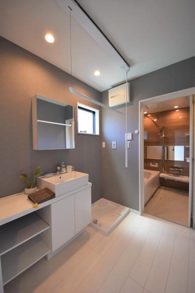 洗面脱衣所は、スッキリ清潔感ある印象に。造作洗面とグレーのクロスで、オトナチュラルを意識。